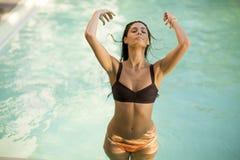 Recht junge Frau, die auf dem Poolside relaxcing ist stockbild