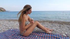 Recht junge Frau, die auf dem Strand durch das Meer schmierig mit Sonnenschutzmittel 4K sitzt stock video footage