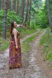 Recht junge Frau, die auf dem Waldweg steht Lizenzfreie Stockfotos