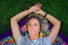 Recht junge Frau, die auf den Rasen auf einem bunten Schal legt lizenzfreies stockbild