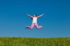 Recht junge Frau, die auf grünes Gras springt Stockbilder