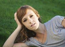Recht junge Frau, die auf Gras liegt lizenzfreie stockfotografie