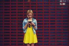 Recht junge Frau, die auf ihrem Smartphone gegen hellen Hintergrund des leeren Kopienraumes für Ihren Inhalt oder Textnachricht p Lizenzfreie Stockbilder