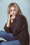 Recht junge Frau, die auf tragender Strickjacke des Bodens sitzt Lizenzfreie Stockfotografie