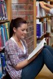 Recht junge Frau, die ein Buch auf dem Fußboden liest Lizenzfreie Stockfotos