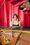 Recht junge Frau, die ein großartiges Klavier spielt Stockbild
