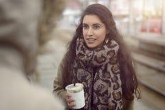 Recht junge Frau, die ein Mitnehmergetränk hält lizenzfreie stockbilder