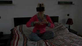 Recht junge Frau, die ein Spiel unter Verwendung der virtuellen Gläser im Schlafzimmer spielt stock video footage