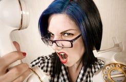 Recht junge Frau, die in ein Telefon kreischt Stockbilder