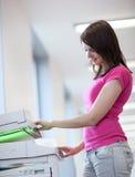 Recht junge Frau, die eine Exemplarmaschine verwendet Stockbild