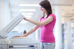 Recht junge Frau, die eine Exemplarmaschine verwendet Stockfotos