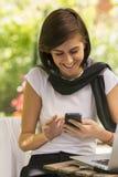 Recht junge Frau, die einen Smartphone verwendet stockfotografie