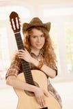 Recht junge Frau, die Gitarre umarmt Stockfoto