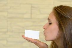 Recht junge Frau, die an Hand eine leere Karte küsst Lizenzfreie Stockfotografie