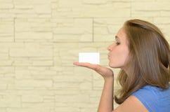 Recht junge Frau, die an Hand eine leere Karte küsst Stockfoto