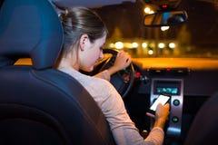 Recht junge Frau, die ihr intelligentes Telefon beim Fahren ihres Autos verwendet Stockbild