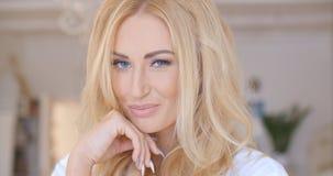 Recht junge Frau, die ihr langes blondes Haar hält Lizenzfreies Stockbild