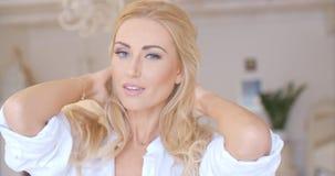 Recht junge Frau, die ihr langes blondes Haar hält Stockbilder