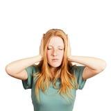 Recht junge Frau, die ihre Ohren abdeckt lizenzfreies stockbild