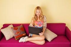 Recht junge Frau, die ihren Laptop bei der Entspannung auf einem Sofa verwendet Stockbild