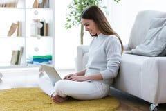 Recht junge Frau, die ihren Laptop beim auf dem Boden zu Hause sitzen verwendet Lizenzfreies Stockfoto