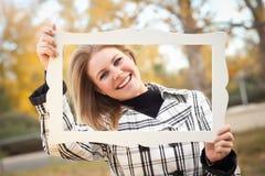 Recht junge Frau, die im Park mit Bilderrahmen lächelt Stockbild