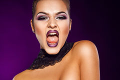 Recht junge Frau, die im Studio auf purpurrotem Hintergrund schreit Stockbild