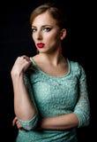 Recht junge Frau, die im tadellosen grünen Kleid aufwirft stockfoto