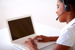 Recht junge Frau, die an Kundendienst arbeitet Lizenzfreies Stockfoto