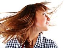 Recht junge Frau, die langes Haar in Luft schleudert Stockbild