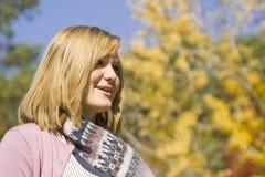 Recht junge Frau, die mit Schal im Herbst lächelt Lizenzfreie Stockfotos