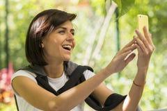 Recht junge Frau, die selfie am Park nimmt lizenzfreie stockfotografie