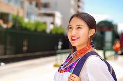 Recht junge Frau, die traditionelle Andenbluse und blauen Rucksack, Wartebus an der Freienstationsplattform trägt Lizenzfreie Stockbilder