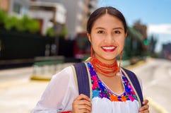 Recht junge Frau, die traditionelle Andenbluse und blauen Rucksack, Wartebus an der Freienstationsplattform trägt Stockbilder