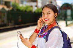 Recht junge Frau, die traditionelle Andenbluse und blauen Rucksack, Wartebus an der Freienstationsplattform trägt Lizenzfreie Stockfotos