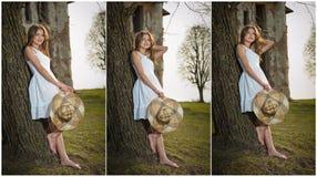 Recht junge Frau, die vor dem Bauernhof aufwirft. Sehr attraktives blondes Mädchen mit dem weißen kurzen Kleid, das einen Hut hält Stockfotos