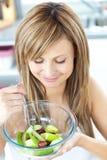 Recht junge Frau, die zu Hause einen Fruchtsalat isst Lizenzfreie Stockfotografie