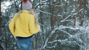 Recht junge Frau in einer gelben Jacke läuft um einen Winterwald stock footage