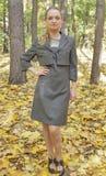 Recht junge Frau in einer grauen Geschäftskleiderstellung Stockfotos