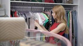 Recht junge Frau geht nahe Gestellen im Kleidungsshop und aufpassende Kleider und Zubehör im Verkauf würzt im Mall stock video