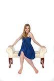 Recht junge Frau im blauen Kleid, das auf Bank sitzt stockbild
