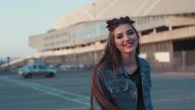 Recht junge Frau im Freizeitkleidungsgehen, in den Drehungen zur Kamera und in den Aktien ein helles glückliches Lächeln Den Spaß stock video footage