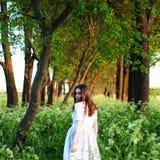Recht junge Frau im langen weißen Kleid und mit langer goldener Locke Stockfotos