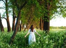 Recht junge Frau im langen weißen Kleid und mit langer goldener Locke Stockfotografie