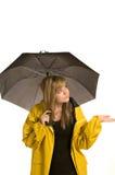 Recht junge Frau im Regenmantel mit Regenschirm Stockfotos