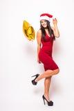 Recht junge Frau im roten Kleider- und Sankt-Weihnachtshut mit Goldsternförmigem Ballon Stockfotos