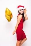 Recht junge Frau im roten Kleider- und Sankt-Weihnachtshut mit Goldsternförmigem Ballon Lizenzfreie Stockfotos