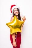 Recht junge Frau im roten Kleider- und Sankt-Weihnachtshut mit Goldsternförmigem Ballon Lizenzfreie Stockbilder
