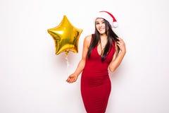 Recht junge Frau im roten Kleider- und Sankt-Weihnachtshut mit Goldsternförmigem Ballon Stockbilder