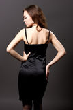 Recht junge Frau im schwarzen Kleid Stockbild